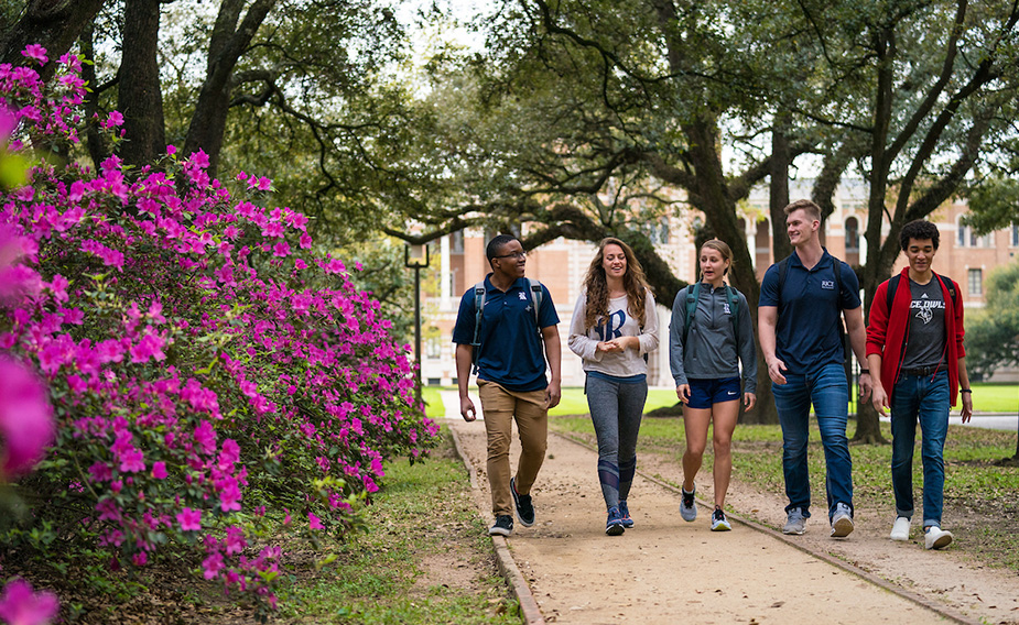 Five Rice students walking on campus pathway